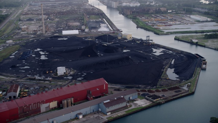 5K aerial  video approach petroleum coke piles by the Calumet River, East Side Chicago, Illinois Aerial Stock Footage | AX0001_169