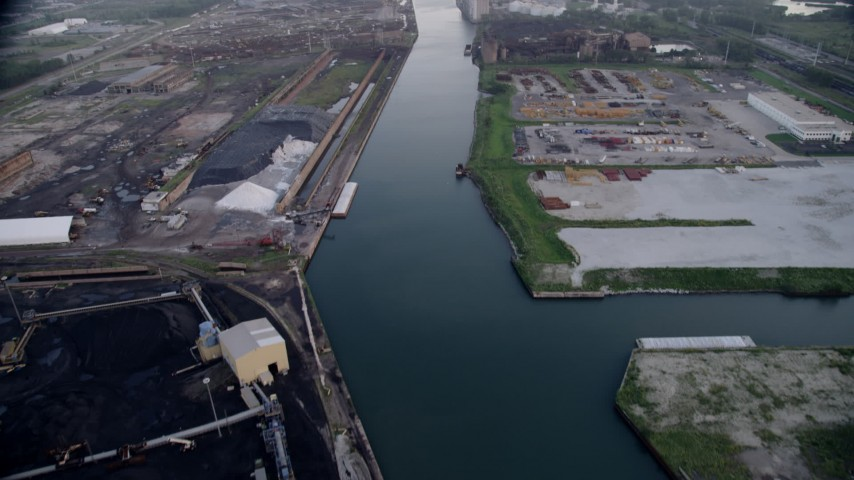 5K aerial  video tilt from bird's eye of petroleum coke by the Calumet River, revealing more industrial buildings, East Side Chicago, Illinois Aerial Stock Footage | AX0001_170