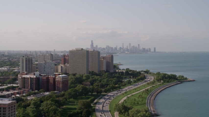 5K stock footage aerial video tilt from Lake Michigan revealing Hyde Park apartment buildings, and the Downtown Chicago skyline, Illinois Aerial Stock Footage | AX0002_003