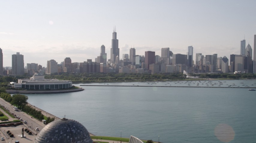 5K stock footage aerial video tilt from Lake Michigan to reveal Adler Planetarium and Astronomy Museum and Downtown Chicago skyline, Illinois Aerial Stock Footage | AX0002_004