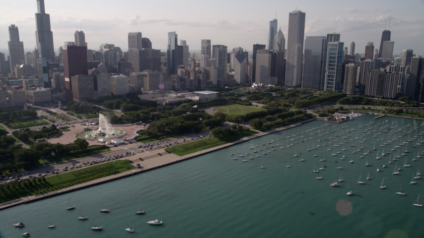 5K stock footage aerial video tilt from boats in the harbor to reveal Grant Park and Downtown Chicago, Illinois Aerial Stock Footage | AX0002_005