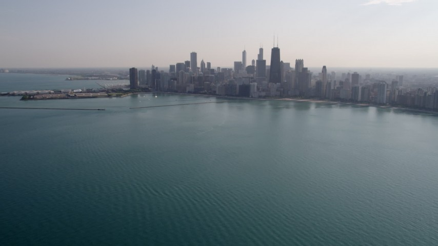 5K stock footage aerial video tilt from Lake Michigan, revealing Downtown Chicago skyline, Illinois Aerial Stock Footage | AX0002_018