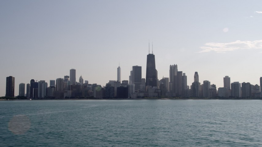 Fly low over Lake Michigan and tilt to reveal the skyline of Downtown Chicago, Illinois Aerial Stock Footage | AX0002_019