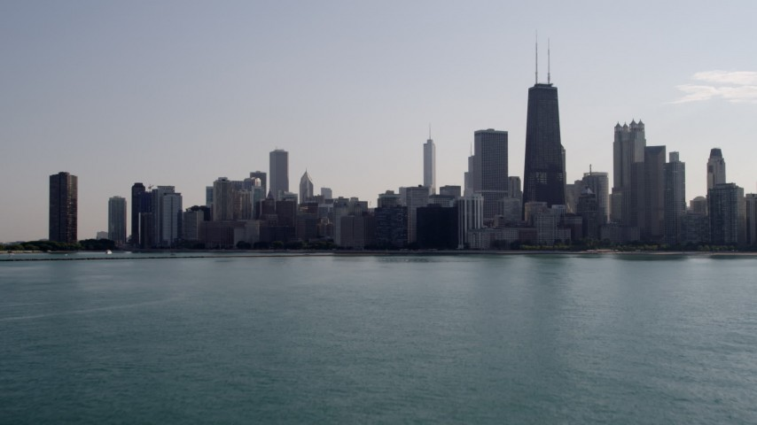 5K stock footage aerial video of flying low over Lake Michigan, tilt up to reveal Downtown Chicago, Illinois Aerial Stock Footage | AX0002_020