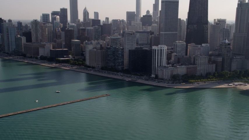 5K stock footage aerial video tilt from Lake Michigan revealing John Hancock Center and Downtown Chicago skyscrapers, Illinois Aerial Stock Footage | AX0002_022