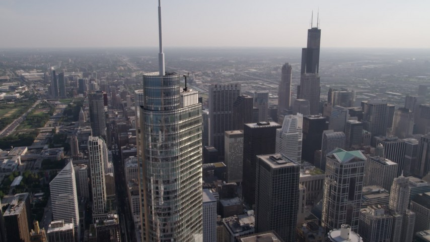 5K stock footage aerial video tilt from Tribune Tower to reveal and approach Trump Tower Chicago and Willis Tower, Downtown Chicago, Illinois Aerial Stock Footage | AX0002_027