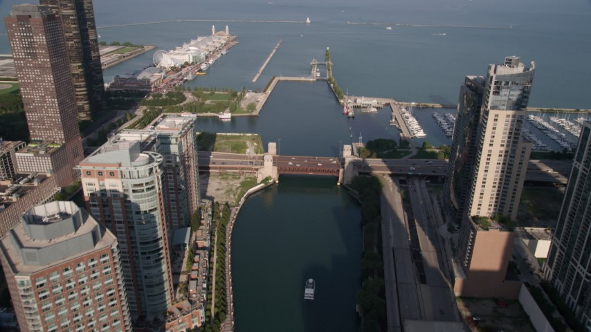 5K stock footage aerial video follow the river through downtown, tilt and approach Navy Pier and Lake Michigan, Downtown Chicago, Illinois Aerial Stock Footage | AX0002_042
