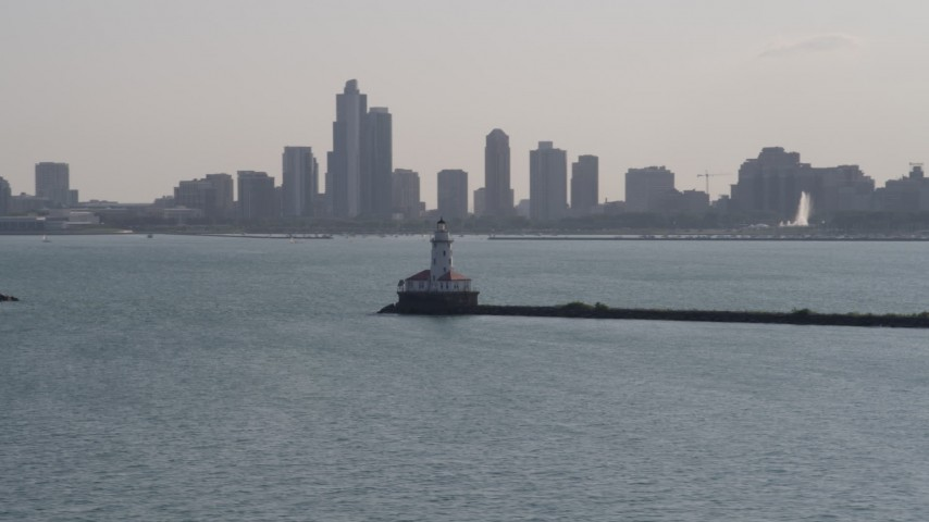 5K stock footage aerial video of orbiting Chicago Harbor Lighthouse with the Downtown Chicago skyline in the background, Illinois Aerial Stock Footage | AX0002_047