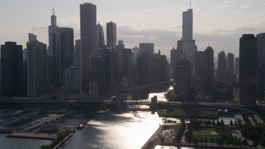 Approach skyline and bridge over Chicago River, with sun reflecting on water, Downtown Illinois Aerial Stock Footage | AX0002_051