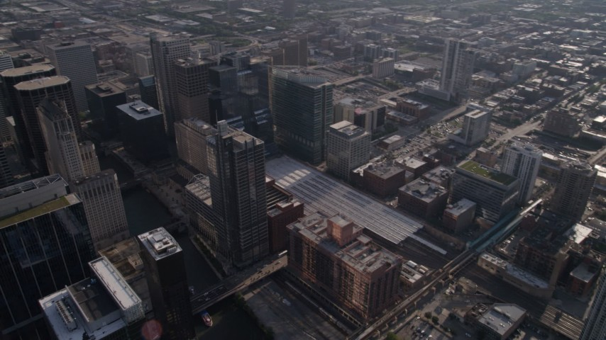 Following the Chicago River through downtown to train station and pan left to follow river, Downtown Illinois Aerial Stock Footage | AX0002_056