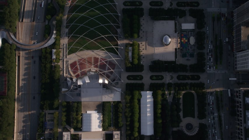 A bird's eye view of the Jay Pritzker Pavilion and the Cloud Gate sculpture in AT&T Plaza, Downtown Chicago, Illinois Aerial Stock Footage | AX0002_080