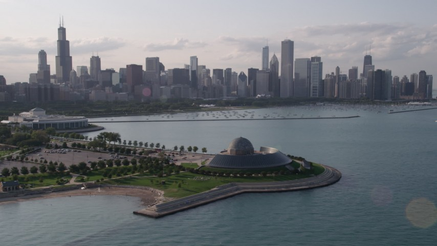 Orbiting the Adler Planetarium and Astronomy Museum with the Downtown Chicago skyline and harbor in background, Illinois Aerial Stock Footage | AX0002_086