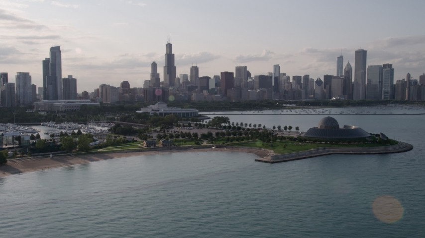 The Downtown Chicago skyline seen while flying by Adler Planetarium and Astronomy Museum, Illinois Aerial Stock Footage | AX0002_088