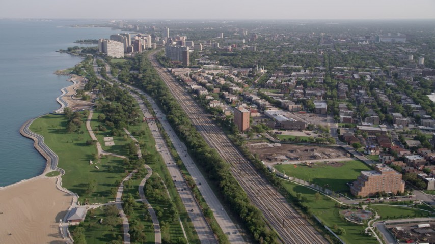 5K stock footage aerial video follow Highway 41 and train tracks toward Hyde Park waterfront apartment buildings, Chicago, Illinois Aerial Stock Footage | AX0002_092