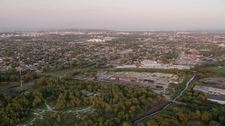 5K stock footage aerial video of a Hammond residential neighborhood and warehouse buildings, on a hazy day, at sunset, Hammond, Indiana Aerial Stock Footage | AX0003_008