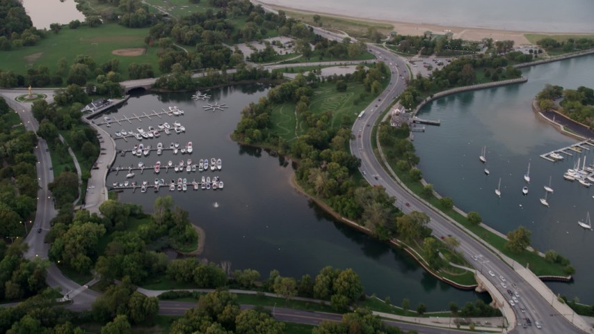 Flying over Jackson Park Harbor, tilt up revealing Museum of Science and Industry, at twilight, Chicago, Illinois Aerial Stock Footage | AX0003_017