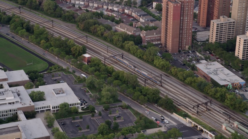 5K stock footage aerial video of tracking a commuter train passing by Hyde Park, at twilight, Chicago, Illinois Aerial Stock Footage | AX0003_020