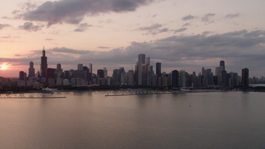 The Downtown Chicago skyline at sunset seen from Lake Michigan, Illinois Aerial Stock Footage AX0003_030
