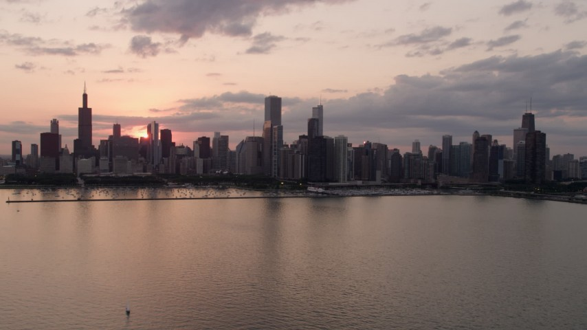 Flying by the skyline from over Lake Michigan, Downtown Chicago, Illinois, sunset Aerial Stock Footage | AX0003_031