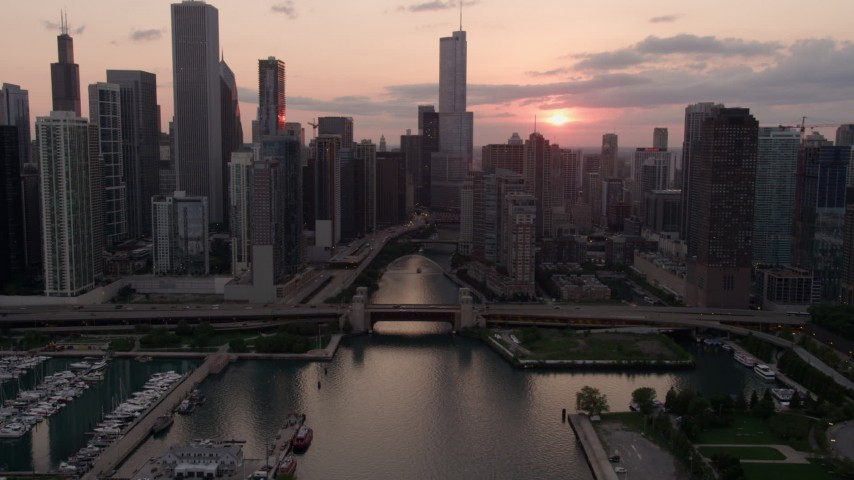 The surface of Lake Michigan, revealing Downtown Chicago, at sunset with clouds, Illinois Aerial Stock Footage AX0003_034