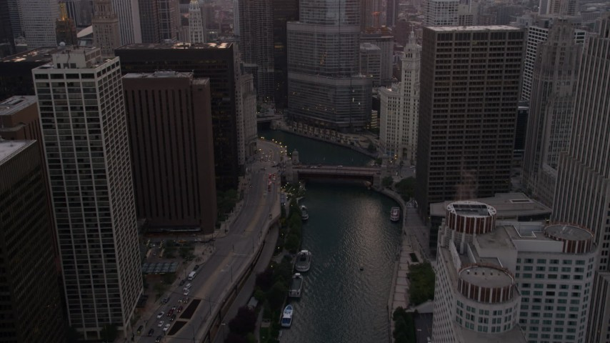 5K stock footage aerial video of following the river toward base of Trump Tower at sunset, Downtown Chicago, Illinois Aerial Stock Footage | AX0003_037