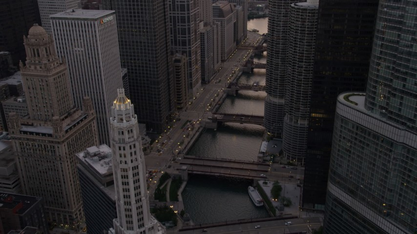 Following the Chicago River between Mather Tower and Trump Tower, at sunset, Downtown Chicago, Illinois Aerial Stock Footage | AX0003_038