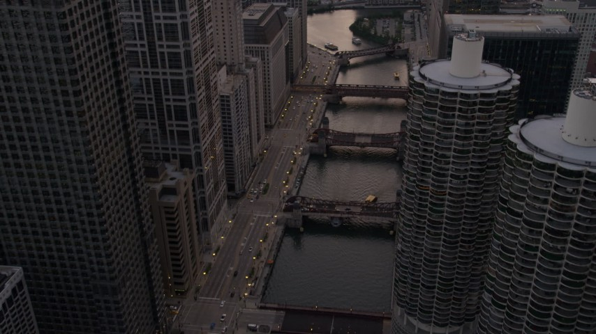 5K stock footage aerial video of following the river through downtown past Marina City at sunset, Downtown Chicago, Illinois Aerial Stock Footage | AX0003_039