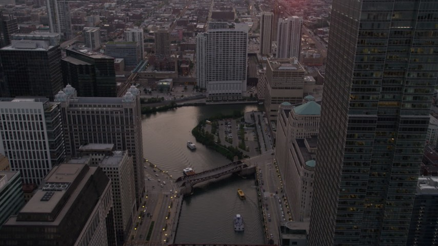 5K stock footage aerial video follow the river through downtown toward 333 N Canal Street at sunset, Downtown Chicago, Illinois Aerial Stock Footage | AX0003_040