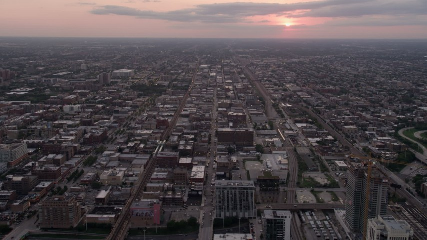 5K stock footage aerial video follow W Fulton Street over apartment buildings in West Chicago at sunset with clouds, Illinois Aerial Stock Footage | AX0003_042
