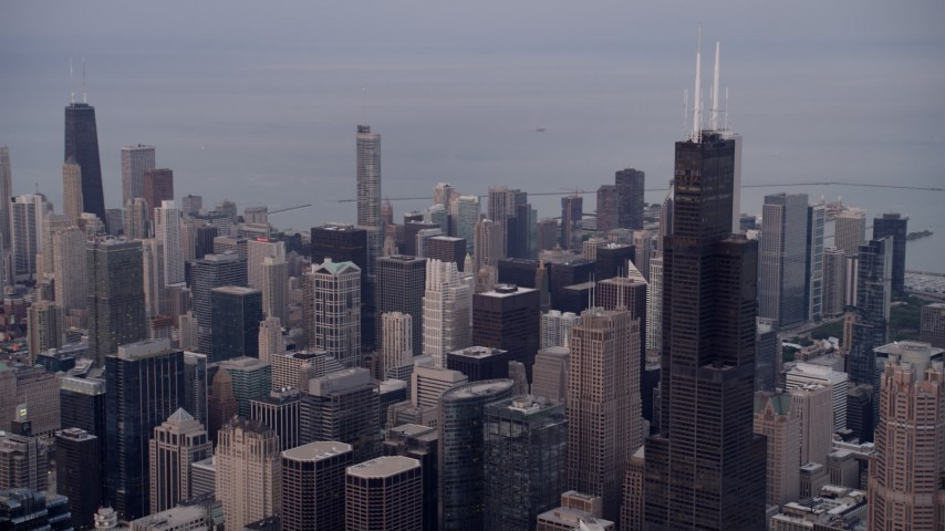Flyby Willis Tower, reveal John Hancock Center in the distance, cloudy, Downtown Chicago, Illinois, sunset Aerial Stock Footage | AX0003_043