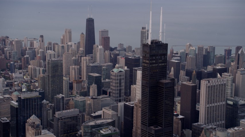 Flying near Willis Tower with a view across the cityscape to John Hancock Center at sunset, Downtown Chicago, Illinois Aerial Stock Footage | AX0003_044