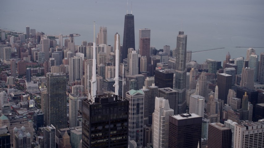 5K stock footage aerial video approach spires atop Willis Tower with a view of the cityscape of Downtown Chicago at sunset, Illinois Aerial Stock Footage | AX0003_045