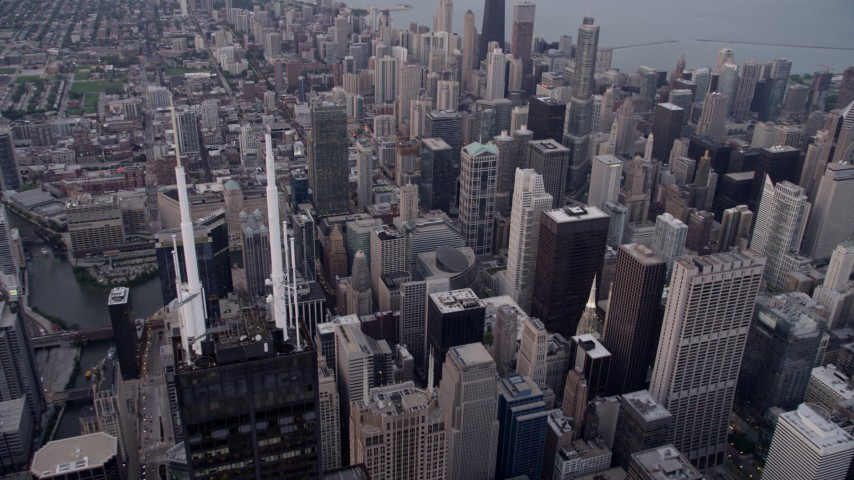 Flying by Willis Tower spires, tilt down to Downtown Chicago buildings, Illinois, sunset Aerial Stock Footage | AX0003_046
