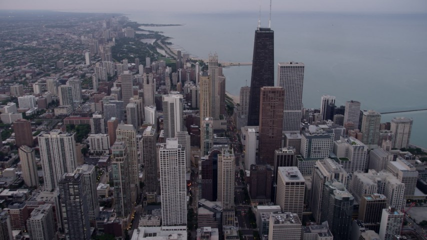 5K stock footage aerial video of flying over Downtown Chicago, approach John Hancock Center on a cloudy day at sunset, Illinois Aerial Stock Footage | AX0003_050