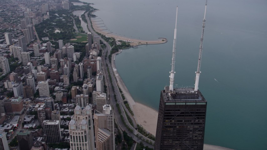 5K stock footage aerial video of flying over top of John Hancock Center, with a view of Lake Shore Drive at sunset, Downtown Chicago, Illinois Aerial Stock Footage   AX0003_052