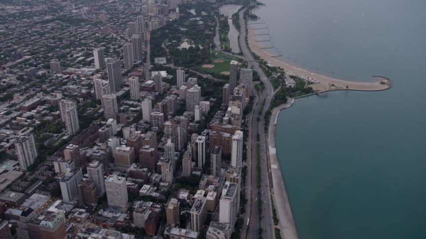 5K stock footage aerial video follow Lake Shore Drive by apartment buildings, and tilt to Lincoln Park at sunset, North Chicago, Illinois Aerial Stock Footage | AX0003_053
