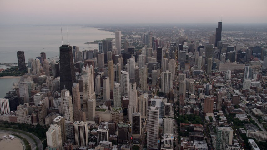 Flying by the cityscape of Downtown Chicago at sunset, Illinois Aerial Stock Footage | AX0003_054