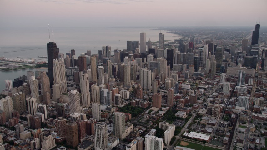 5K stock footage aerial video of Downtown Chicago cityscape and John Hancock Center, on a cloudy day at sunset, Illinois Aerial Stock Footage | AX0003_055