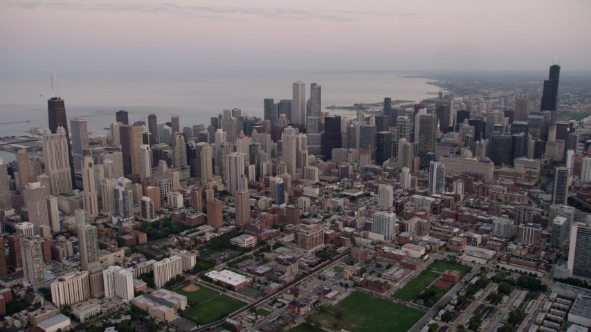 A wide view of the Chicago cityscape by Lake Michigan, Downtown Chicago, Illinois, sunset Aerial Stock Footage | AX0003_056