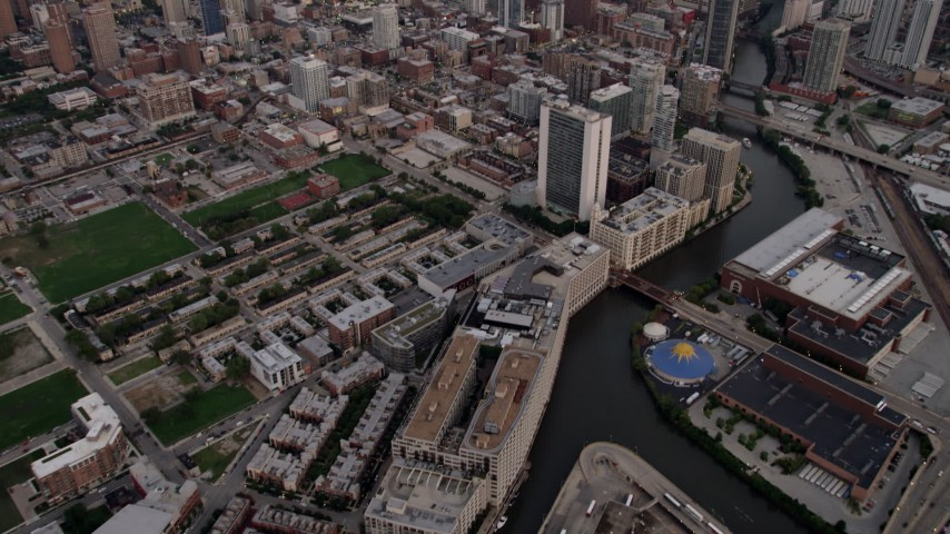 5K stock footage aerial video tilt from apartments by the Chicago River, revealing Downtown Chicago at sunset, Illinois Aerial Stock Footage | AX0003_057