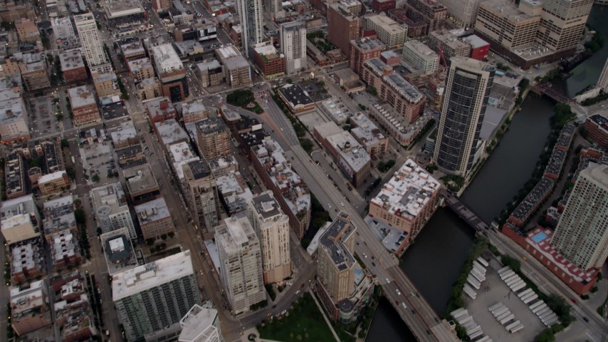 Tilt from the Chicago River to reveal and approach Downtown Chicago skyscrapers at sunset, Illinois Aerial Stock Footage | AX0003_058