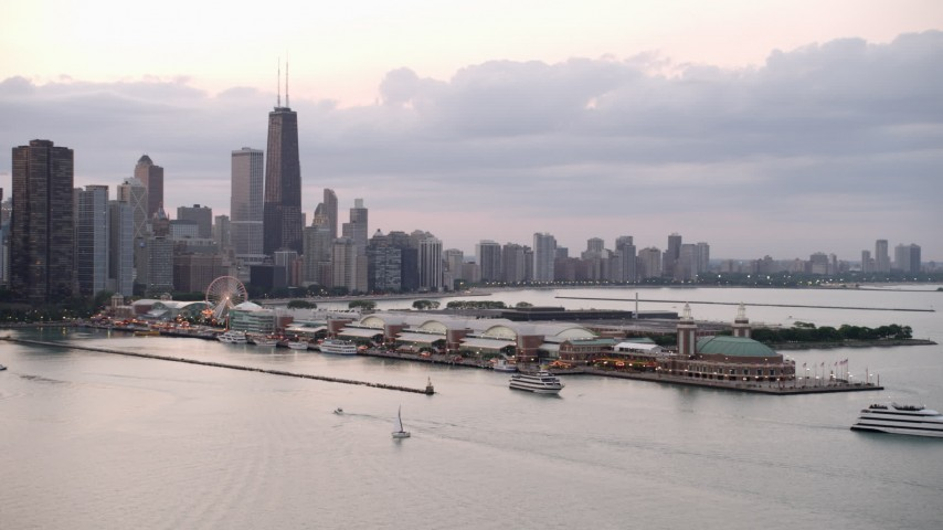 Orbit Navy Pier, revealing Downtown Chicago skyline, on a cloudy day at sunset, Illinois Aerial Stock Footage | AX0003_064