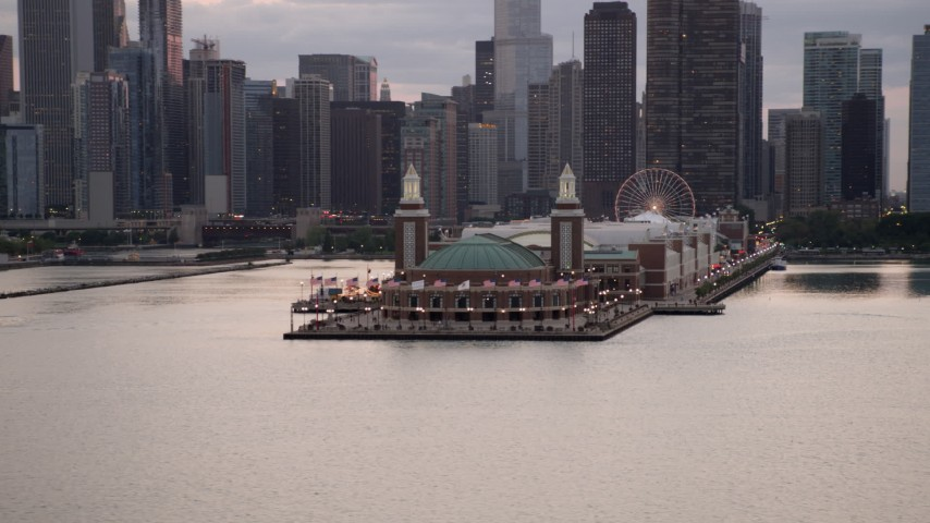 Flying by Navy Pier with Ferris wheel, with Downtown Chicago behind it, on a cloudy day at sunset, Illinois Aerial Stock Footage | AX0003_066