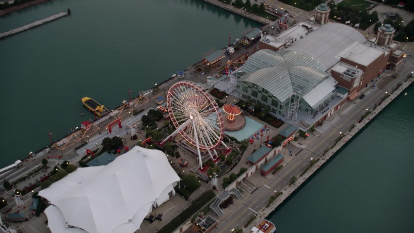 5K stock footage aerial video tilt to Ferris wheel and amusement park rides on Navy Pier, at sunset, Chicago, Illinois Aerial Stock Footage   AX0003_068