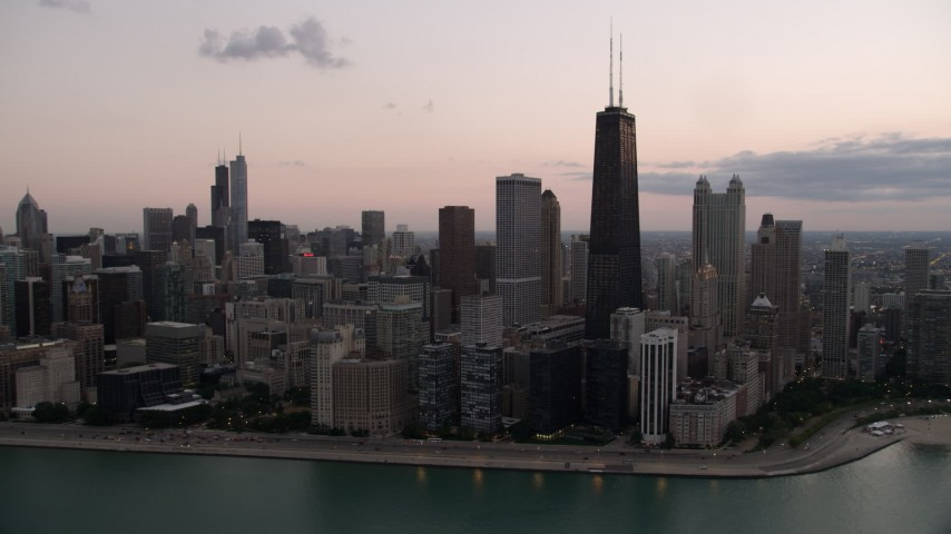 5K stock footage aerial video of John Hancock Center and lakefront skyscrapers, seen from Lake Michigan, with clouds at twilight, Illinois Aerial Stock Footage | AX0003_070