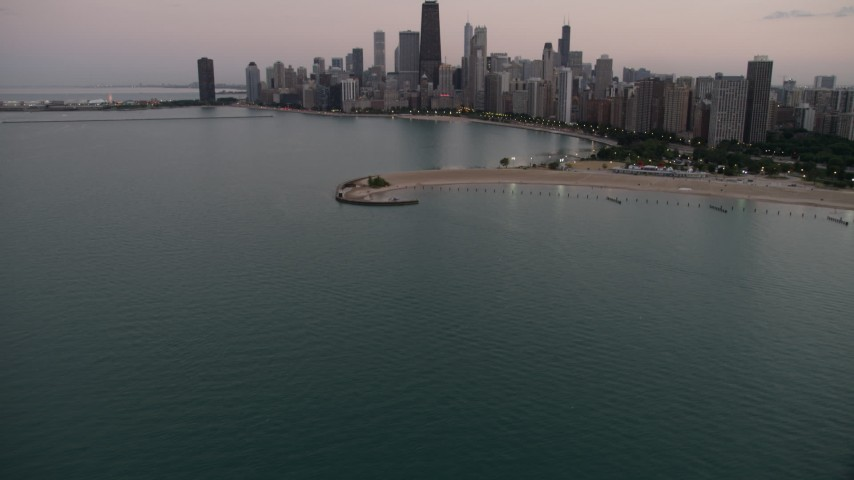 5K stock footage aerial video tilt from Lake Michigan, revealing North Avenue Beach and Downtown Chicago skyline, at twilight, Illinois Aerial Stock Footage | AX0003_072