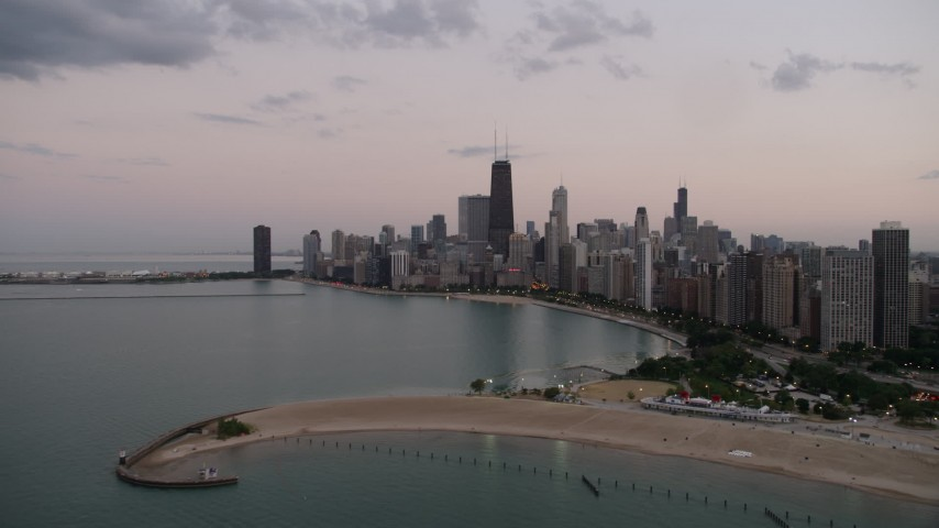 5K stock footage aerial video approach North Avenue Beach and the skyline of Downtown Chicago, on a cloudy day at twilight, Illinois Aerial Stock Footage | AX0003_073