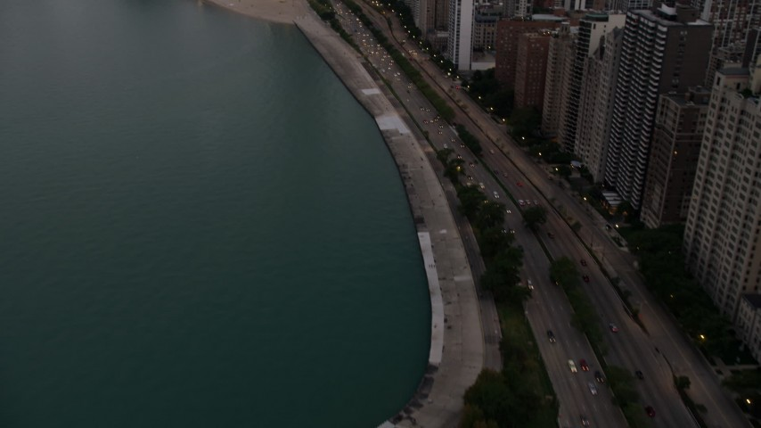 5K stock footage aerial video tilt from Lake Shore Drive, revealing Downtown Chicago buildings, on a cloudy day at sunset, Illinois Aerial Stock Footage | AX0003_074