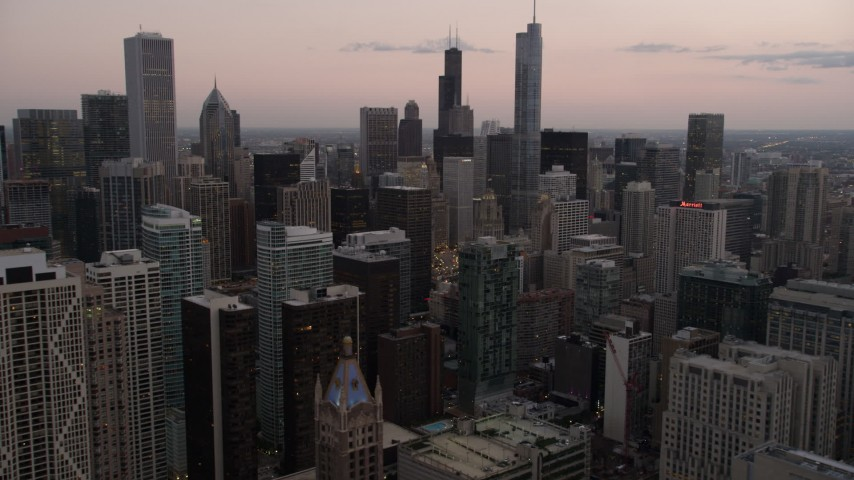 Passing by Downtown Chicago skyscrapers at sunset, Illinois Aerial Stock Footage | AX0003_078