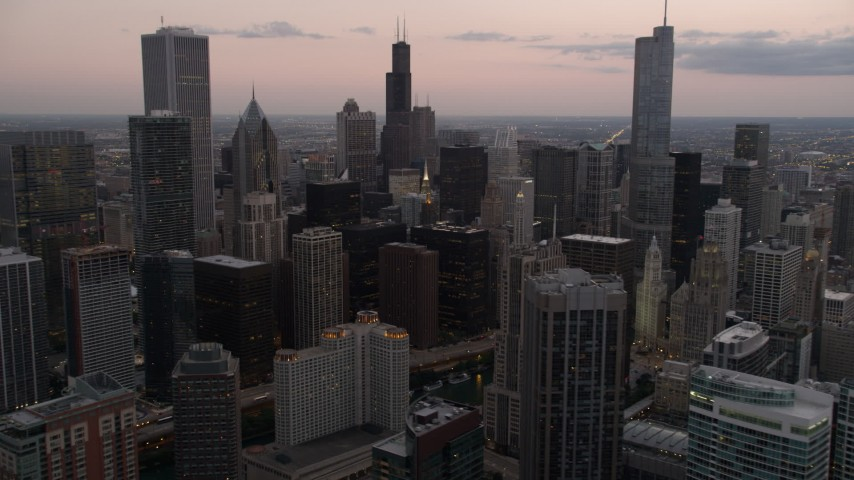 Flyby skyscrapers and high-rises at sunset in Downtown Chicago, Illinois and reveal the Chicago River Aerial Stock Footage | AX0003_079